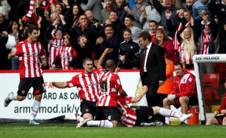 Sheffield United's manager Danny Wilson looks on as Stephen Quinn is congratulated on scoring by the opening goal of the game by his team-mates