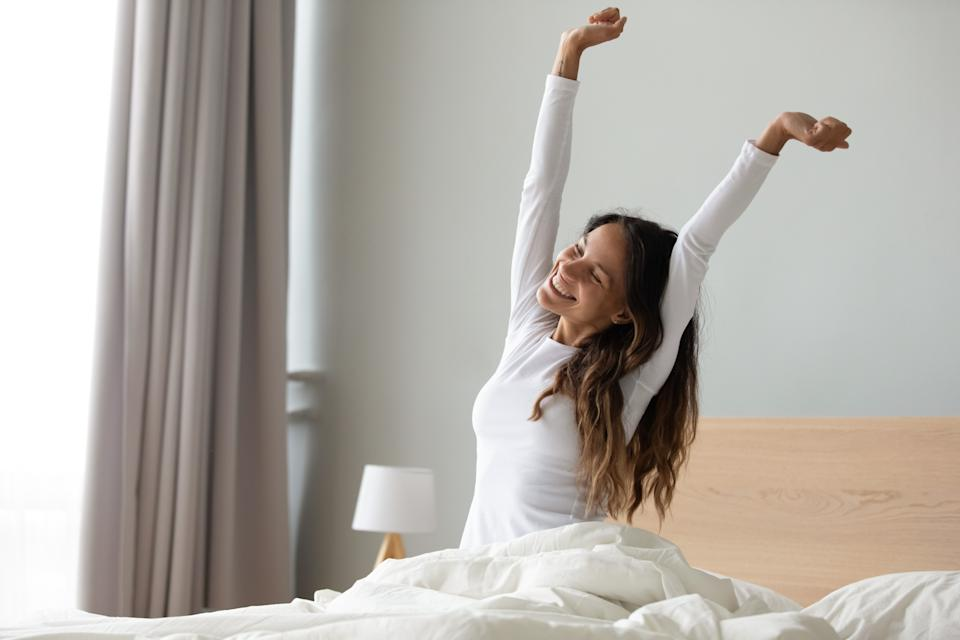Happy woman in white nightwear sitting in bed awakened from enough and healthy sleep feels good