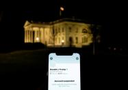 A photo illustration shows the suspended Twitter account of U.S. President Donald Trump on a smartphone and the White House in Washington