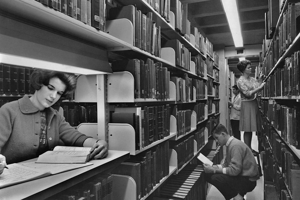 <p>College students spend time in the library stacks to get some research done. </p>