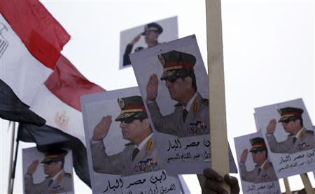 Posters of Army Chief General Abdel Fattah al-Sisi are seen as supporters of the army protest against ousted Islamist President Mohamed Mursi and members of the Muslim Brotherhood at the tomb of late Egyptian President Anwar Sadat, during the 40th anniversary of Egypt's attack on Israeli forces in the 1973 war, at Cairo's Nasr City district, October 6, 2013. REUTERS/Amr Abdallah Dalsh