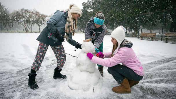 PHOTO: Children from the Hoffman and Lynns families build a snowman on the public basketball courts in Forsyth Park, Jan. 3, 2018, in Savannah, Ga. (Stephen B. Morton/AP)