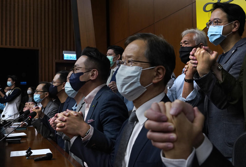 Hong Kong's pro-democracy legislators holding hands pose a picture during a press conference at the Legislative Council in Hong Kong, Monday, Nov. 9, 2020. The lawmakers said Monday that they would resign en masse if Beijing disqualifies any of them. The announcement came amid unconfirmed reports that Beijing would oust four legislators for filibustering meetings and violating their oath. (AP Photo/Vincent Yu)