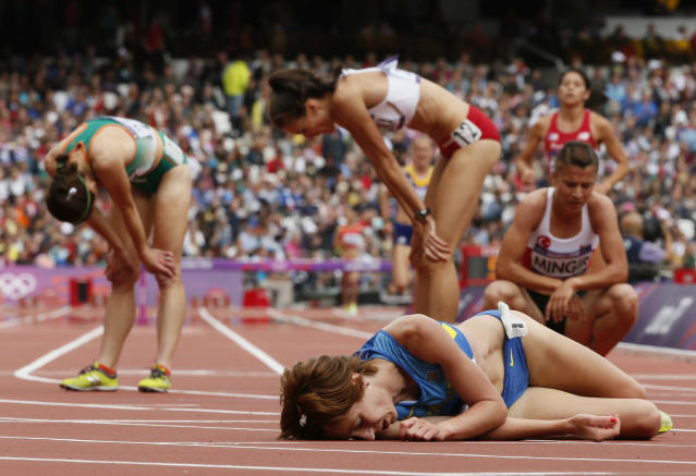 Ukraine's Valentyna Horpynych Zhudina (C) lies on the track as other athletes recover after their women's 3000m steeplechase round 1 heats at the London 2012 Olympic Games at the Olympic Stadium August 4, 2012. REUTERS/Lucy Nicholson (BRITAIN - Tags: OLYMPICS SPORT ATHLETICS TPX IMAGES OF THE DAY)