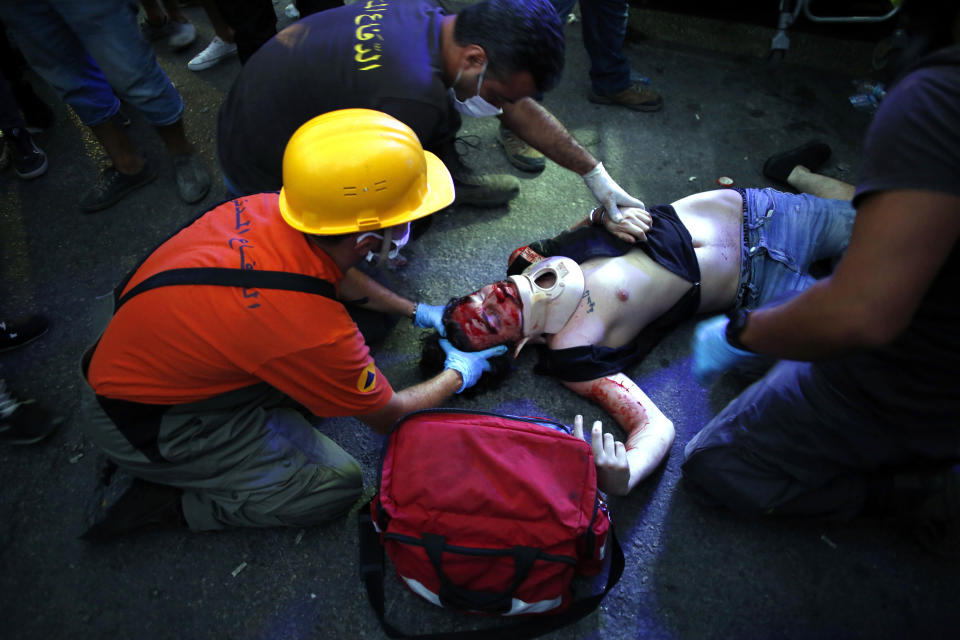 A injuried protestor lies on the floor during clashes with police as part of a protest against the political elites and the government after this week's deadly explosion at Beirut port which devastated large parts of the capital in Beirut, Lebanon, Saturday, Aug. 8, 2020. (AP Photo/Thibault Camus)