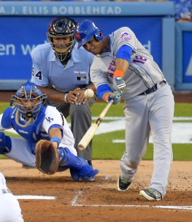 New York Mets' Juan Lagares, right, hits a three-run home run in front of Los Angeles Dodgers catcher Drew Butera and home plate umpire CB Bucknor during the fourth inning of a baseball game, Saturday, Aug. 23, 2014, in Los Angeles. (AP Photo/Mark J. Terrill)