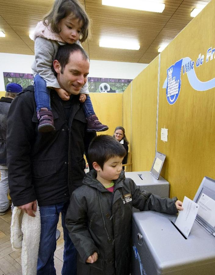 A young boy casts his father's ballot at a polling station in Fribourg, western Switzerland, on October 18, 2015 (AFP Photo/Fabrice Coffrini)
