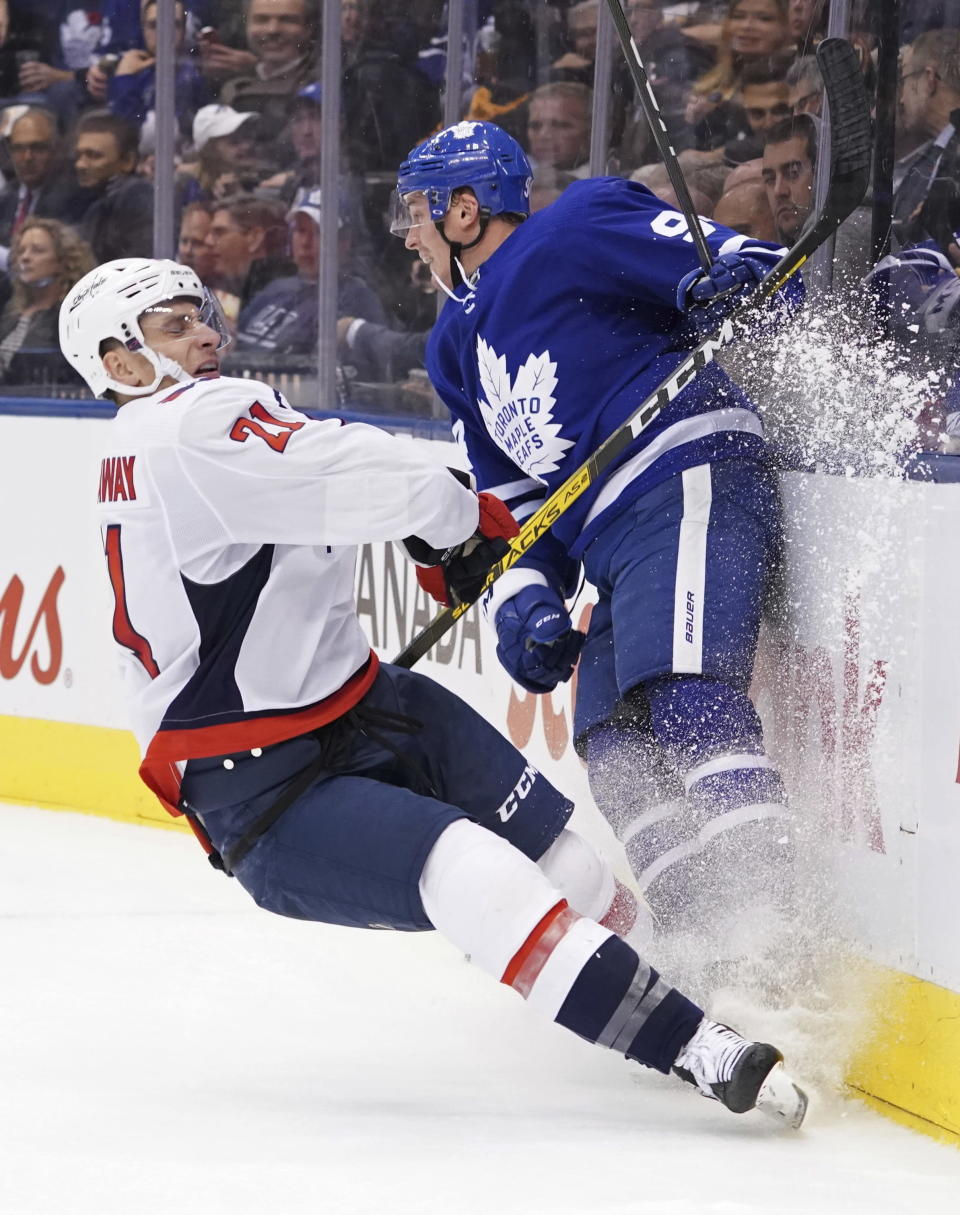 Washington Capitals right wing Garnet Hathaway (21) crashes into the boards with the Toronto Maple Leafs defenseman Tyson Barrie (94) during the first period of an NHL hockey game Tuesday, Oct. 29, 2019, in Toronto. (Hans Deryk/The Canadian Press via AP)