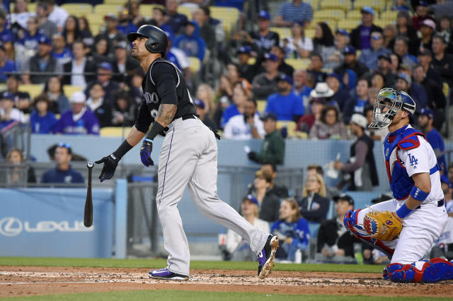 Colorado Rockies' Ian Desmond leaves the batter's box on a solo home run as Los Angeles Dodgers catcher Yasmani Grandal watches during the second inning of a baseball game Tuesday, May 22, 2018, in Los Angeles. (AP Photo/Mark J. Terrill)