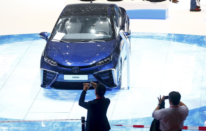 People take pictures of Toyota Mirai car ahead of the 85th International Motor Show in Geneva