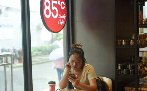 A woman looks at her mobile phone at a 85C Bakery Cafe in Hangzhou in China's eastern Zhejiang province - Credit: AFP