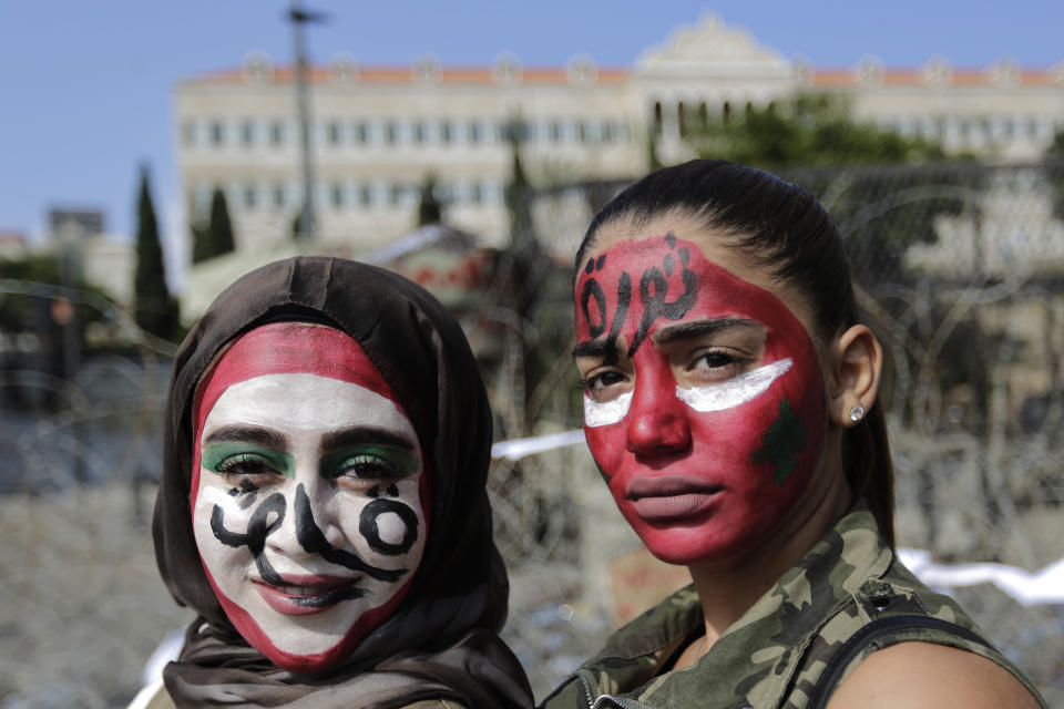 "Anti-government protesters with the colors of the Lebanese national flag painted on their faces and with Arabic that reads ""Revolution,"" pose for a photograph in front of the government palace in Beirut, Lebanon, Monday, Oct. 21, 2019. Protesters have closed major roads around Lebanon ahead of an emergency Cabinet meeting to discuss a rescue plan for the country's crumbling economy. AP Photo/Hassan Ammar)"