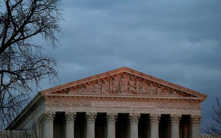 The top of U.S. Supreme Court building is lit at dusk in Washington