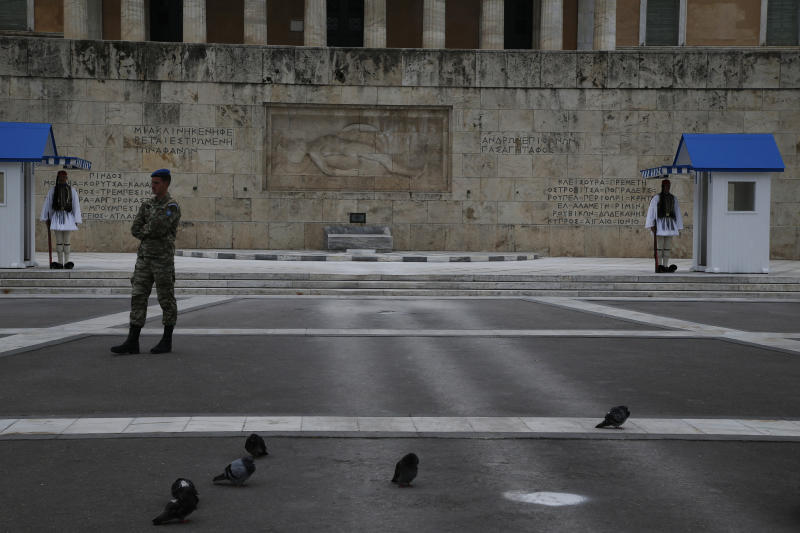 Presidential Guards stand in front of the Greek parliament, in central Athens, Sunday, March 22, 2020. Schools, restaurants, and other public places are already closed in the Greek capital aimed at slowing the spread of the new coronavirus, but other places like supermarkets, pharmacies and gas stations remain open.  The COVID-19 illness causes mild or moderate symptoms in most people, but severe symptoms are more likely in the elderly or those with existing health problems. (AP Photo/Lefteris Pitarakis)