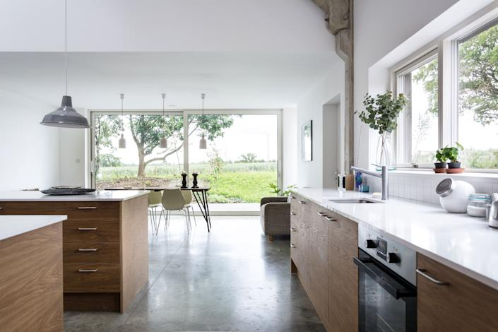 "<div class=""caption""> The scale of the barn is revealed in the main studio and open-plan kitchen. The lowered ceiling height in the adjoining dining area is intimate yet expansive, opening onto the garden and landscape beyond. </div>"