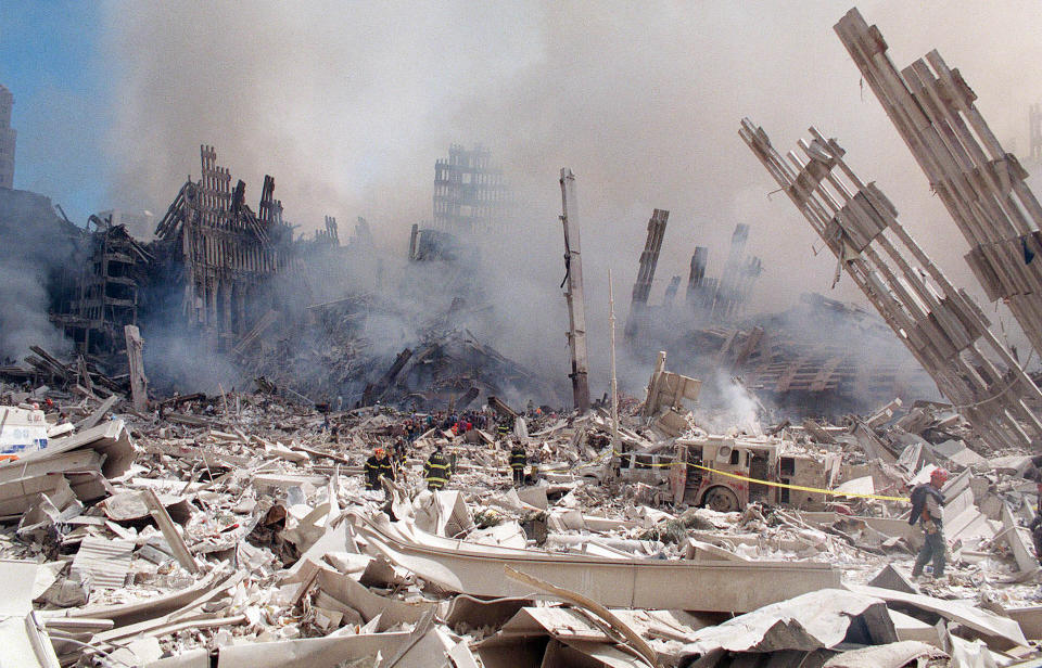 FILE — In this Sept. 12, 2001 file photo, firefighters work in the rubble of the World Trade Center towers in New York. Two decades after the twin towers' collapse, people are still coming forward to report illnesses that might be related to the attacks. (AP Photo/Virgil Case, File)