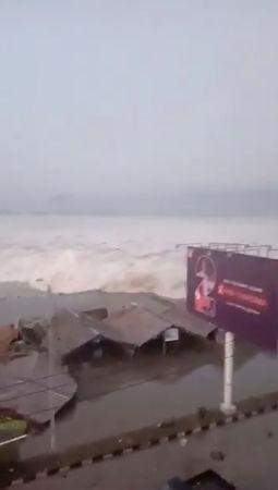 A tsunami wave hits shore in Palu, Indonesia Sulawesi Island, in this September 28, 2018 photo by AMAS. AMAS/Social Media/via REUTERS
