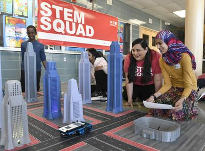 Kim Gonzales, second from right, of Texas Instruments' STEM Squad, and Khudaijah Amin, a Parkville Middle School seventh-grader, program a robotic car with the new TI-Nspire CX II graphing calculator on Wednesday, March 6, 2019 in Baltimore. TI's STEM Squad is traveling the country getting students excited students about math, science and engineering. (Steve Ruark/AP Images for Texas Instruments)