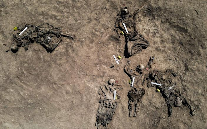 Graphic content: This aerial view taken on June 13, 2021, shows human remains, reportedly of victims of the 2014 Badush prison massacre committed by the Islamic State (IS) group, after being unearthed from a mass grave in the northern Iraqi village of Badush, northwest of the city of Mosul. - In June 2014, IS fighters attacked the prison, freeing Sunnis and loading the remaining 600 mainly Shiite inmates onto trucks, before driving them to a ravine and shooting them. - ZAID AL-OBEIDI/AFP