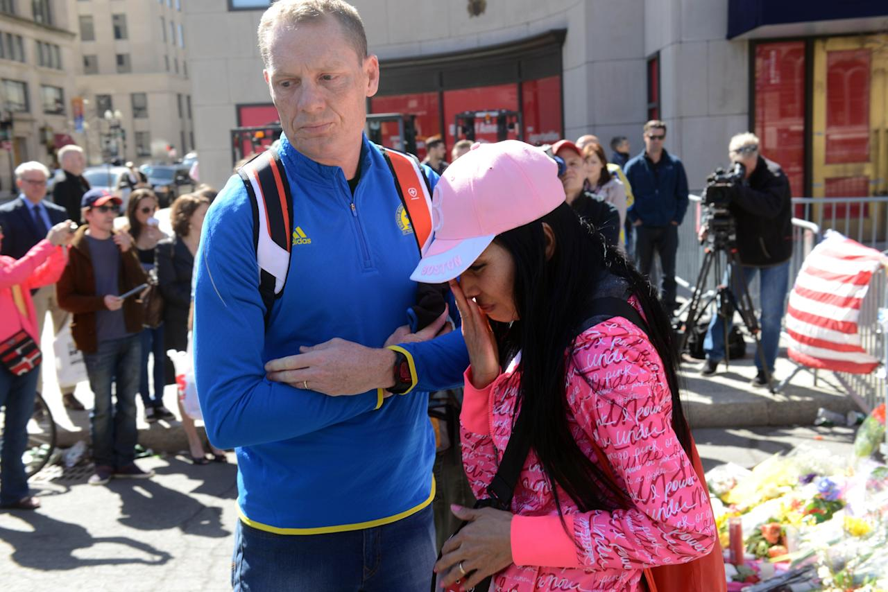 BOSTON, MA - APRIL 17: A man and woman leave after pausing at the makeshift memorial on Boylston Street to the victims of the Boston Marathon bombing April 17, 2013 in Boston, Massachusetts. Boston continues to return to normal, as businesses and streets are reopened following two bomb explosions at the finish line of the marathon that killed 3 people and injured over a hundred more. (Photo by Darren McCollester/Getty Images)