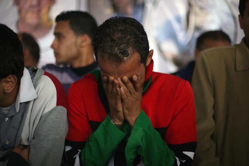 A Libyan man, wearing the colors of the pre-Gadhafi flag, weeps for his brother at a funeral in Benghazi, Libya, Monday, March 5, 2012 for victims buried in a mass grave. Thousands of mourners gathered Monday in the eastern Libyan city of Benghazi to bury 155 bodies unearthed from a mass grave of people were killed during last year's civil war. It was the largest grave yet to be discovered from the conflict that began as a popular uprising and ended with the capture and killing of Libyan leader Moammar Gadhafi last October.(AP Photo/Manu Brabo)