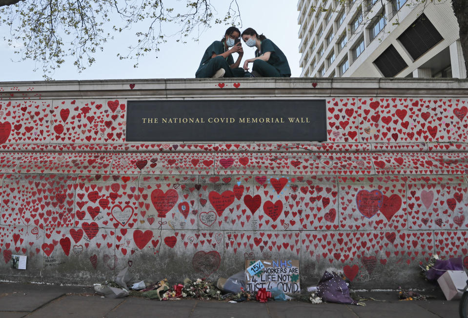 FILE - In this Tuesday, April 27, 2021 file photo, nurses from the nearby St Thomas' hospital sit atop the National Covid Memorial Wall in London. British Prime Minister Boris Johnson has on Wednesday, May 12 confirmed that an independent public inquiry into the government's handling of the coronavirus pandemic will start hearing evidence next year. While welcoming the announcement, a leading group representing the bereaved think it should begin sooner. (AP Photo/Frank Augstein, file)