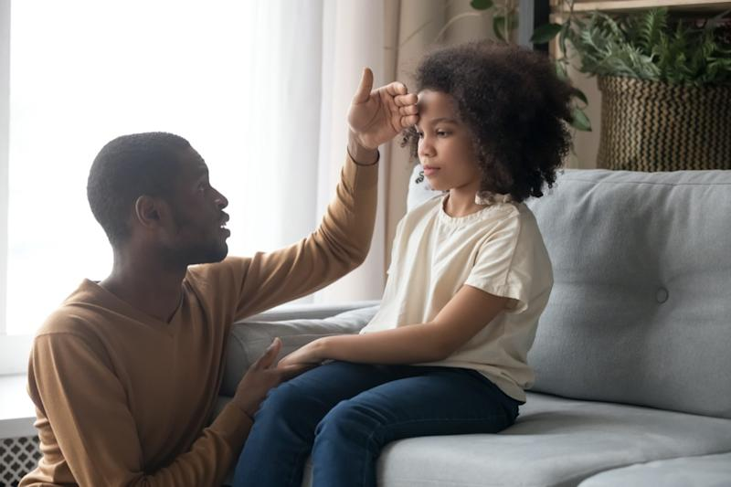 Worried dad father check temperature touch forehead of unhealthy schoolgirl daughter sitting on sofa at home