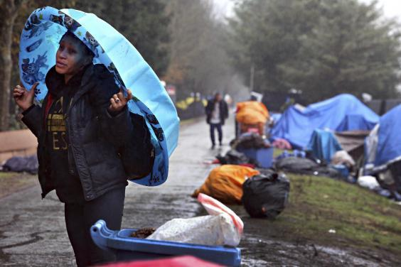 A resident takes cover from the rain (AP)
