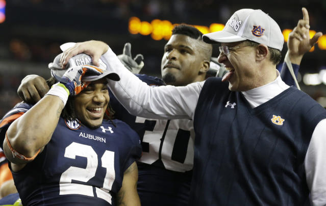 Auburn running back Tre Mason (21) and Auburn head coach Gus Malzahn celebrate after the second half of the Southeastern Conference NCAA football championship game against the Missouri, Saturday, Dec. 7, 2013, in Atlanta. Auburn won 59-42. (AP Photo/John Bazemore)