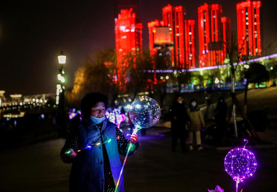 A vendor decorates a balloon for sale by a river on New Year's Eve in Wuhan (Reuters)