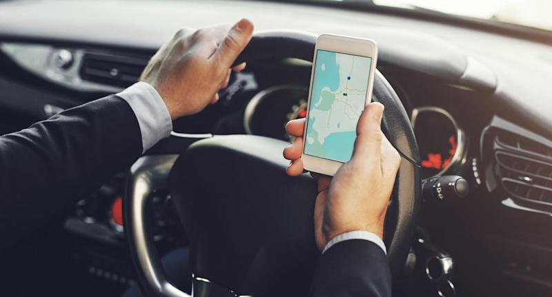 A stock image of a man is pictured using his mobile phone to look at a map while driving. NSW will be rolling out cameras to catch drivers on their mobile phones.