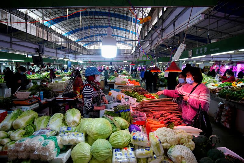 FILE PHOTO: People wearing face masks buy vegetables at a wet market, following an outbreak of the coronavirus disease (COVID-19) in Wuhan
