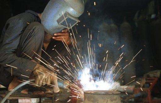 An Indian labourer welds metal in an industrial area of Mumbai. India's industrial output growth rebounded by a surprise 2.4 percent in May after shrinking the previous month, data showed Thursday, bringing some cheer after a string of gloomy economic numbers