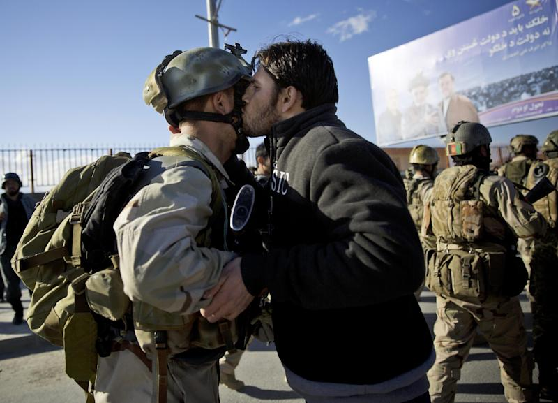 An Afghan special forces soldier, left, is kissed by an Afghan man after the commandos took over control of an election office after the Taliban launched an assault with a suicide bomber detonating his vehicle outside an election office in Kabul, Afghanistan, Tuesday, March 25, 2014. Gunmen stormed into the building, trapping dozens of employees inside and killing many people. A candidate for a seat on a provincial council was among those killed, along with an election worker, a civilian and a policeman. (AP Photo/Anja Niedringhaus)