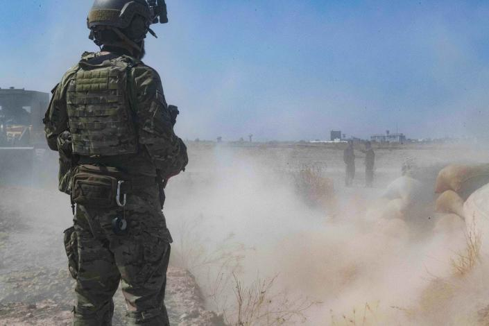 """In this Sept. 21, 2019, photo, released by the U.S. Army, a U.S. soldier oversees members of the Syrian Democratic Forces as they demolish a Kurdish fighters' fortification as part of the so-called """"safe zone"""" near the Turkish border. (U.S. Army photo by Staff Sgt. Andrew Goedl via AP)"""