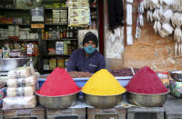 A shopkeeper wears a face mask as a precaution against the coronavirus waits for customers at a market in Bengaluru, India, Friday, Nov. 20, 2020. India's total number of coronavirus cases since the pandemic began has crossed 9 million. Nevertheless the country's new daily cases have seen a steady decline for weeks now and the total number of cases represents 0.6% of India's 1.3 billion population. (AP Photo/Aijaz Rahi)
