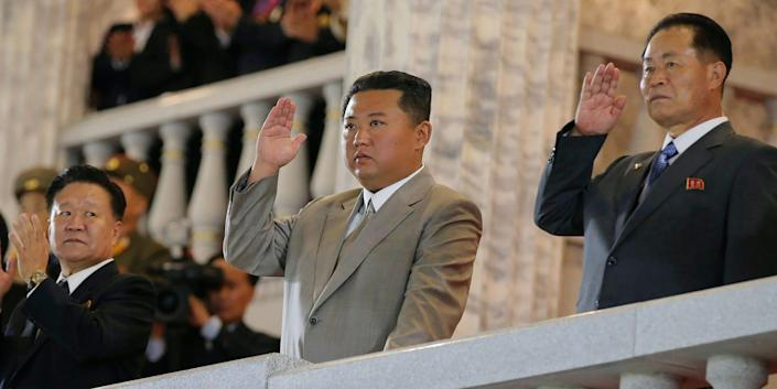 Kim Jong Un and two officials hold their hands up in salute from a balcony above a military parade in Pyongyang, September 2021.