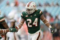 Miami running back Cody Brown (24) is congratulated after scoring s touchdown during the first half of an NCAA college football game against Central Connecticut State, Saturday, Sept. 25, 2021, in Miami Gardens, Fla. (AP Photo/Lynne Sladky)