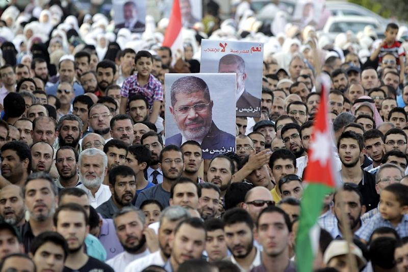 Protesters from the Islamic Action Front take part in a rally in support of deposed Egyptian president Mohamed Mursi (poster) near the Egyptian embassy in the Jordanian capital Amman, on August 14, 2013