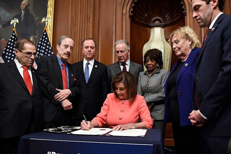 House Speaker Nancy Pelosi signs the resolution to transmit the two articles of impeachment to the Senate for trial. The articles of impeachment against Trump are for abuse of power and obstruction of Congress. | Susan Walsh/AP/Shutterstock