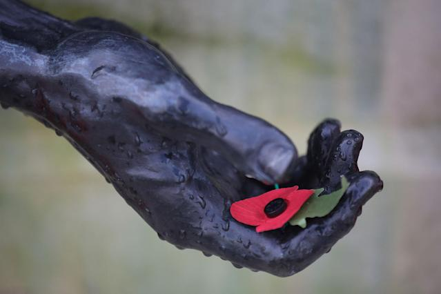 <p>A poppy rests in the hand of a statue during the annual Armistice Day Service at The National Memorial Arboretum on Nov. 11, 2017 in Alrewas, England. (Photo: Christopher Furlong/Getty Images) </p>