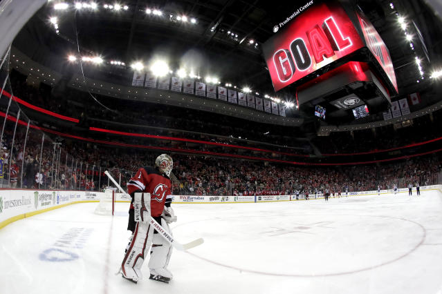 New Jersey Devils goaltender Keith Kinkaid skates near his end of the ice as teammates celebrate a goal by left wing Marcus Johansson, of Sweden, during the first period of an NHL hockey game against the Winnipeg Jets, Saturday, Dec. 1, 2018, in Newark, N.J. (AP Photo/Julio Cortez)