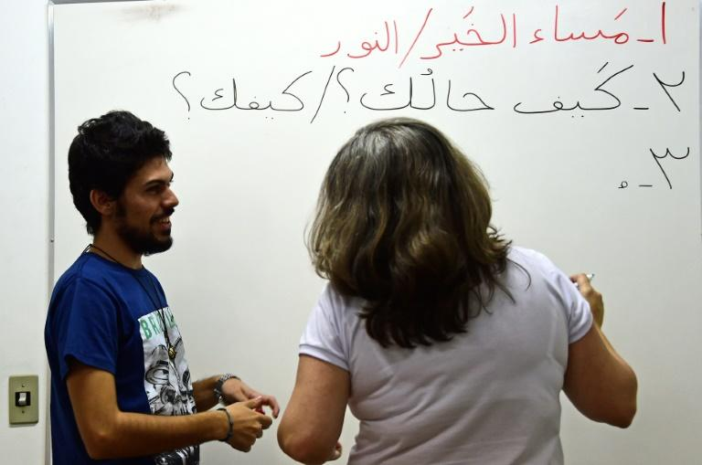 Syrian refugee Adel Bakkour (L) teaches Arabic in Rio de Janeiro, Brazil on April 20, 2017