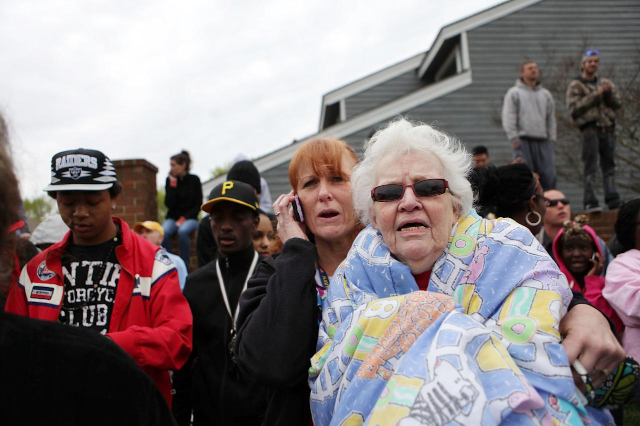 "Elizabeth DeAngelis, right, a resident of the Mayfair Mews Apartments, huddles in a blanket, as her daughter Misty Caine lets a caller know that her mother is fine, after a Navy fighter jet crashed at the apartment complex, Friday, April 6, 2012, in Virginia Beach, Va. Six people, including both pilots, were taken to hospitals, officials said. The Navy said both aviators on board the jet ejected before it crashed around noon and were being taken to hospitals for observation. ""I saw flames and a parachute was hanging off my balcony,"" said DeAngelis about the experience after hearing the crash and going to her balcony to see what had happened. (AP Photo/Virginian-Pilot, Vicki Cronis-Nohe)"