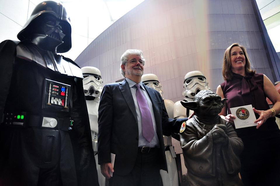 Filmmaking legend George Lucas (L)and Kathleen Kennedy (R) president of Disney's Lucasfilms pose with Stormtroopers (back) and Darth Vader (L) characters from Lucas' Star Wars films at the opening of Disney's Lucasfilms' new animation production facility, the Sandcrawler in Singapore on January 16, 2014. AFP PHOTO / STEFANUS IAN        (Photo credit should read STEFANUS IAN/AFP via Getty Images)