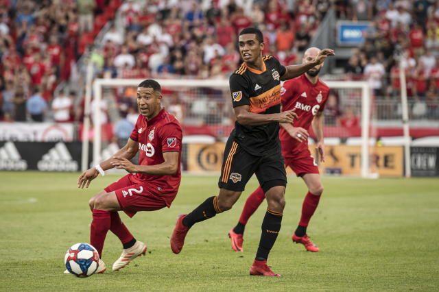 Houston Dynamo midfielder Memo Rodriguez (8) passes the ball under pressure from Toronto FC defender Justin Morrow (2) and teammate Laurent Ciman (26) during the first half of an MLS soccer game, Saturday, July 20, 2019 in Toronto. (Christopher Katsarov/The Canadian Press via AP)