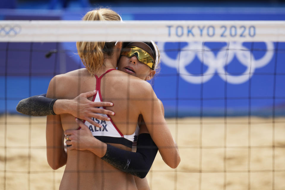 April Ross, right, of the United States, hugs teammate Alix Klineman during a women's beach volleyball match against Germany at the 2020 Summer Olympics, Tuesday, Aug. 3, 2021, in Tokyo, Japan. (AP Photo/Petros Giannakouris)