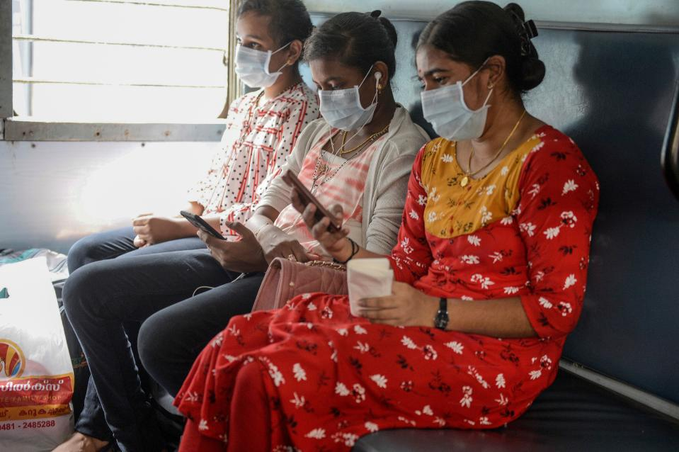Passengers wearing facemasks amid concerns over the spread of the COVID-19 novel coronavirus sit inside a coach of a train at a railway station in Secunderabad, the twin city of Hyderabad, on March 20, 2020. (Photo by NOAH SEELAM / AFP) (Photo by NOAH SEELAM/AFP via Getty Images)