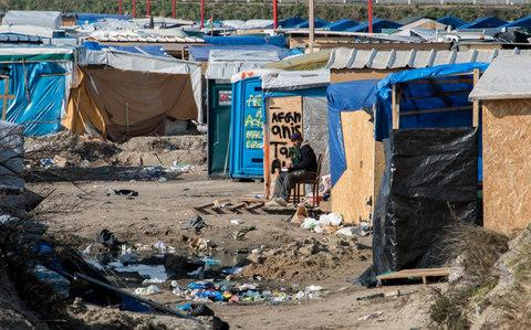 "A man sitting among shacks in the northern part of the so-called ""Jungle"" migrant camp in Calais in March 2016 - Credit:  DENIS CHARLET/DENIS CHARLET Source: AFP"