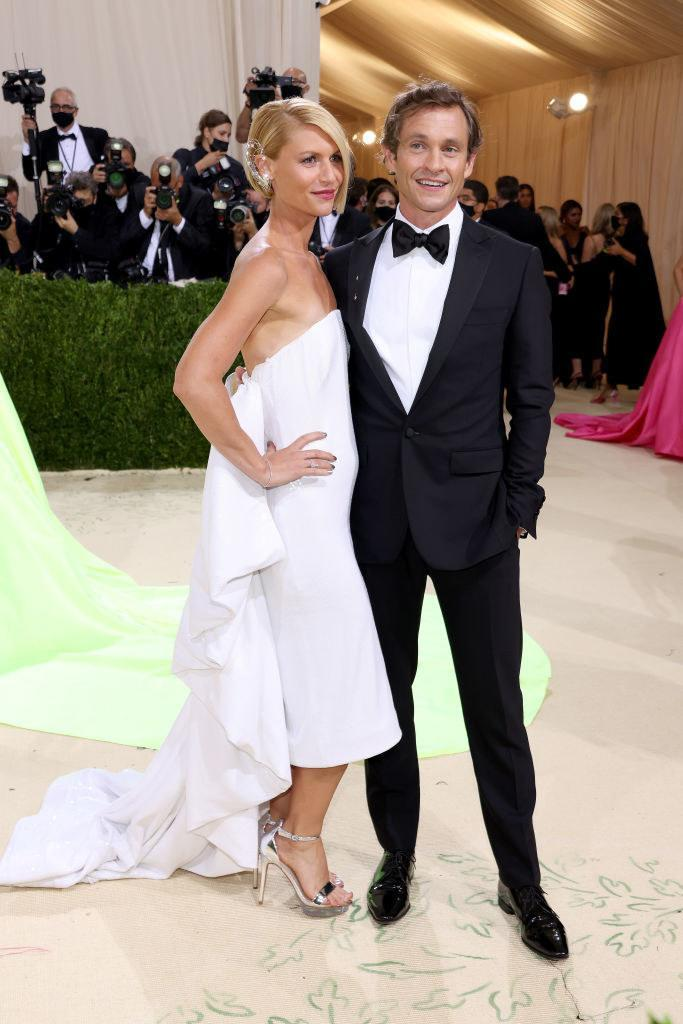 Claire Danes wears a floor length light colored strapless gown and Hugh Dancy wears a dark suit